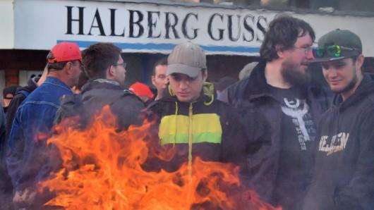 Mitarbeiter des Automobilzulieferers Neue Halberg-Guss streiken vor dem Standort Leipzig hinter einer brennenden Tonne.