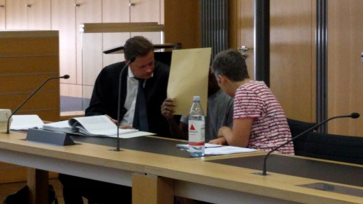 Der Angeklagte versteckt am ersten Verhandlungstag vor dem Braunschweiger Landgericht sein Gesicht hinter einer Mappe (Archivbild).