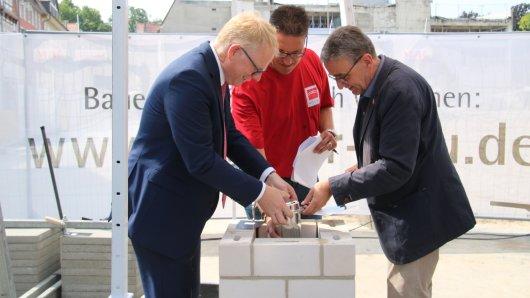 Thomas Pink, Investor Benedikt Schmidt-Wächter und Bauleiter Steffan Schmidt haben am Samstag eine Zeitkapsel im Grundstein des Löwentor-Centers versenkt.