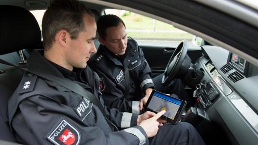 Oberkommissar Daniel Arth (l) und Hauptkommisar Björn Hirsch von der Polizeiinspektion Salzgitter-Peine-Wolfenbüttel sitzen am 05.04.2017 in Salzgitter mit einem Tablet-PC im Einsatzfahrzeug. Die Ermittler testen, ob sich mit der Software Einbrüche vorhersagen und stoppen lassen.