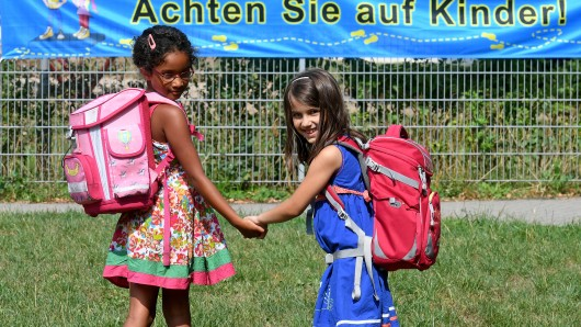 Hannover: Die sieben Jahre alte Schülerin Alicia (l) und die sechs Jahre alte Schülerin Milla stehen vor einem Transparent mit der Aufschrift der Aktion Kleine Füße - sicherer Schulweg Achten Sie auf Kinder!.