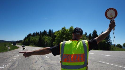 Ein Polizist hält einen Motorradfahrer an (Archivbild).