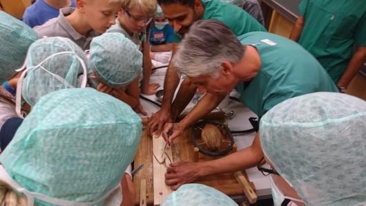 Ärzte zeigen den Kindern, wie eine Kokosnuss operiert wird.