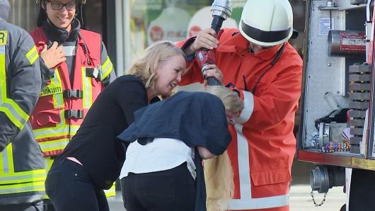 Ein Feuerwehrmann wäscht einer Friseurkundin (r) mit Wasser aus dem Feuerwehrschlauch die Haare aus. Bei einem Brand in einem Einkaufszentrum löschten die Einsatzkräfte am Mittwoch nicht nur ein Feuer, sondern wuschen auch einer Friseurkundin die Haare aus.