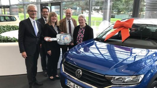 Harald Lesch (v.l.), Vorstandsvorsitzender der VR-Gewinnspargemeinschaft e. V., Carsten Ueberschär, Leiter der Direktion Braunschweig und Heike Bergmann, Kundenberaterin (beide Volksbank BraWo), gratulieren dem Ehepaar Hartmann bei der Fahrzeugübergabe in Wolfsburg.