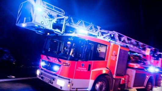 Ein Drehleiterwagen der Feuerwehr fährt mit Blaulicht über eine Straße.