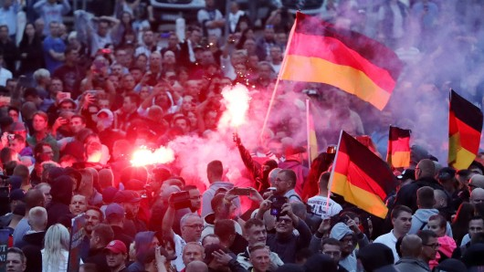 Demonstranten der rechten Szene zünden in Chemnitz Pyrotechnik und schwenken Deutschlandfahnen (Archivfoto).