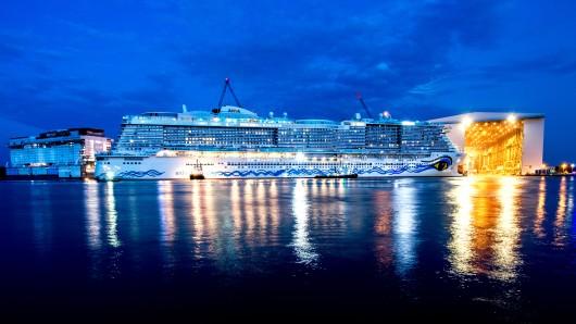 Schlepper ziehen das neue Kreuzfahrtschiff AIDAnova aus der überdachten Werfthalle der Meyer-Werft.