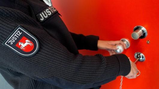 Eine Justizbeamten sperrt eine Gefängniszelle auf (Symbolbild).