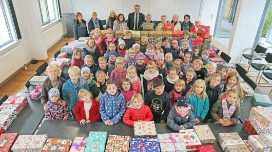 Lehrerinnen, Schülerinnen und Schüler der Grundschule Grasleben und die Weihnachtsdamen übergeben die liebevoll gepackten Schuhkartons an Samtgemeindebürgermeister Gero Janze.