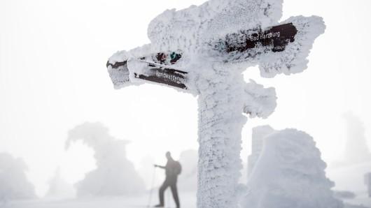 Ein Wanderer mit Wanderstöcken geht an einem vereisten Wegweiser auf dem Brocken vorbei. Weil er auf einer Wanderung im Oberharz auf schneebedecktem Weg gestürzt ist und sich verletzt hat, fordert ein Mann vom Land Schmerzensgeld.