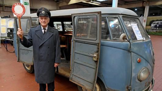 Heinz Scholze steht in historischer Uniform und Winkerkelle vor einem 66 Jahre alten T1 VW-Bulli in der Oldtimersammlung von VW-Nutzfahrzeuge. Der damalige Polizeihauptwachtmeister und spätere Hauptkommissar gehörte zu den Teilnehmern des 2. Radarlehrgangs im Jahr 1961 in Niedersachsen.
