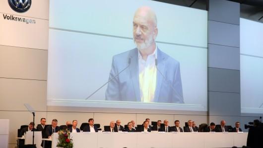Redner Bernd Osterloh während seiner Rede in Halle 11, projiziert auf eine Leinwand hinter der Vorstands-Bank auf der Bühne.