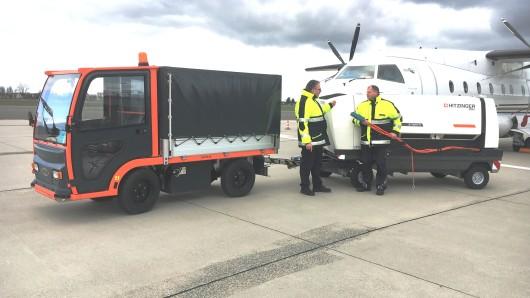 Maik Wermuth (links), Leiter der Technischen Dienste sowie der Werkfeuerwehr, mit seinem Kollegen Maik Ledderbohm an der neuen lärmgedämmte Bodenstromversorgung von Flugzeugen, gezogen von einem Elektroschlepper, auf dem Vorfeld des Flughafens.