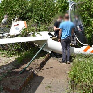 Passanten und Polizisten stehen an einem nach einer Notlandung in einem Kleingartenverein erheblich beschädigtem Segelflugzeug. Bei dem missglückten Landemanöver auf einem an die Kleingarten-Parzellen angrenzenden Segelflugplatz in Helmstedt wurde am Pfingstmontag niemand verletzt.