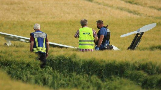 Einsatzkräfte aus dem Harz und aus Braunschweig untersuchen vor Ort den Ort, an dem ein Ultraleichtflugzeug aus bisher unbekannter Ursache über einem Getreidefeld abgestürzt war.
