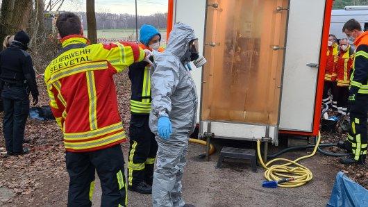 Ein Feuerwehrmann in Schutzkleidung wird nach einem Einsatz in dem Waldstück bei Seevetal in Niedersachsen mit Wasser abgespritzt.
