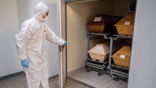 Mitarbeiter Niklas Grube öffnet im Krematorium Celle eine Kühlkammer, in der vier Särge von Verstorbenen stehen, die mit oder an dem Coronavirus gestorben sind.