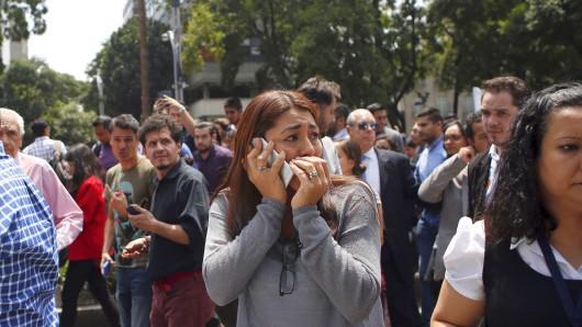 Eine Frau telefoniert am 19.09.2017 in Mexiko-Stadt (Mexiko), nachdem die Mitarbeiter eines Bürogebäudes während des Erdbebens evakuiert worden sind. Genau am Jahrestag des schweren Erdbebens von 1985 ist die Millionenmetropole erneut von einem heftigen Beben erschüttert worden. Die Stärke wurde mit 7,1 angegeben. Das Zentrum lag bei Axochiapan im Bundesstaat Morelos, nur 160 Kilometer südöstlich von der mexikanischen Hauptstadt. Foto: Rebecca Blackwell/AP/dpa +++(c) dpa - Bildfunk+++