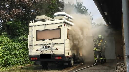 Im dichten Rauch versuchen Feuerwehrleute den Brand zu bekämpfen.