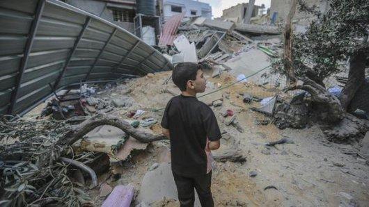 Palästinensische Autonomiegebiete, Gaza: Ein Kind blickt auf die Trümmer des eingestürzten Al-Waleed-Gebäudes, nachdem es am frühen Morgen von einem israelischen Luftangriff getroffen wurde.