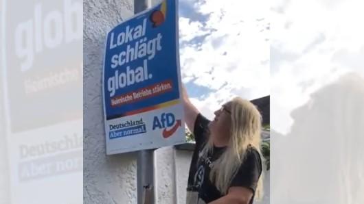 Der Anwohner und Rocker Sven Hieronymus entfernt das AfD-Plakat.