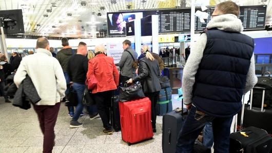 Fluggäste stehen vor den Check-in-Schaltern in der Abflughalle A auf dem Flughafen. In Hannover fallen etwa ein Drittel aller Flüge aus.