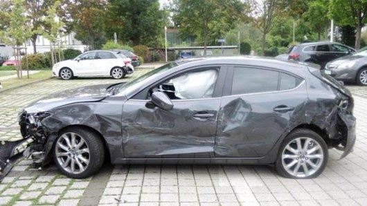 Ein zerstörtes Auto steht auf einem Parkplatz.