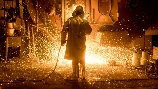 Ein Salzgitter-Mitarbeiter in Schutzkleidung arbeitet an einer sogenannten Stahlpfanne. (Archivbild)