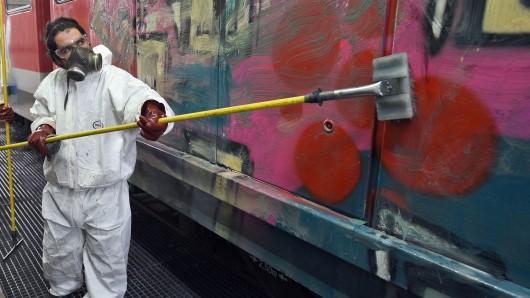 Nervig und teuer: Ein Mann entfernt ein Graffiti von einem Zug (Archivbild).