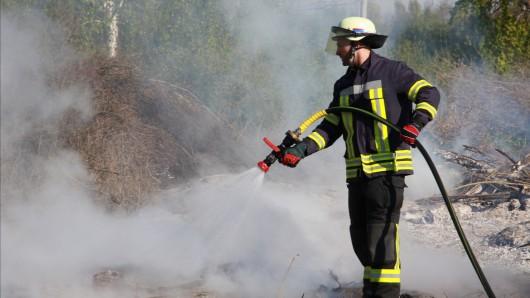 Ein Feuerwehrmann löscht das Osterfeuer beim SV Fortuna Lebenstedt.