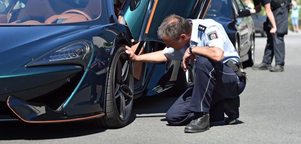 Ein Polizist kontrolliert die Reifen bei einem McLaren. Der Carfreitag ist der traditionelle Saisonstart für die Auto-Tuner.