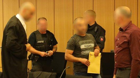Der Angeklagte (mit Mappe) kommt ohne Handschellen in den Saal des Landgerichts Braunschweig.