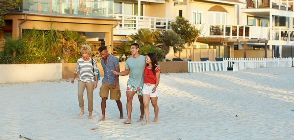 Freunde an Ferienhaus am Strand.