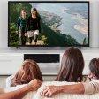 Familie schaut sich im Wohnzimmer auf dem Smart-TV eine Diashow mit Urlaubsbildern an.