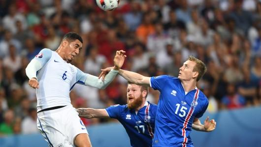 Aron Gunnarsson (Mitte) und Jon Dadi Bodvarsson (rechts) von Island kämpfen mit Chris Smalling um den Ball.