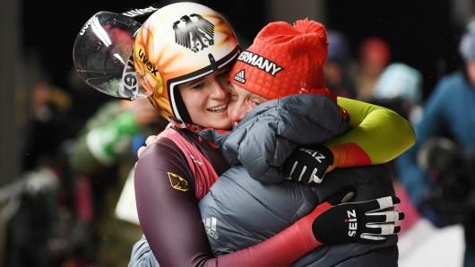 Natalie Geisenberger und der deutsche Rodel-Bundestrainer Norbert Loch jubeln über ihre Goldmedaille und umarmen sich im Ziel.
