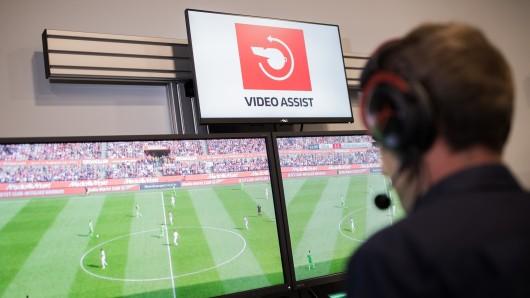 Ein Schiedsrichter sitzt in einem Videoassistcenter vor Monitoren, die Fußball-Spielszenen zeigen (Archivbild).