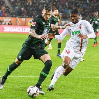 Wolfsburgs Daniel Ginczek im Duell mit FCA-Spieler Kevin Danso.