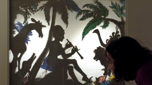 Eine Frau betrachtet im Tübinger Lotte-Reiniger-Museum Silhouettenfiguren, die für das Schattentheater-Stück Die Zauberflöte gefertigt wurden.