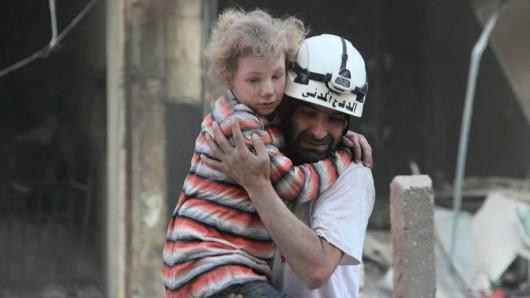 EIn Helfer rettet ein Kind aus einem völlig zerstörten Haus in Aleppo. (Archivbild)