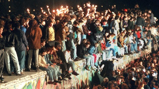 Jubelnde Menschen sitzen am 11.11.1989 mit Wunderkerzen auf der Berliner Mauer.