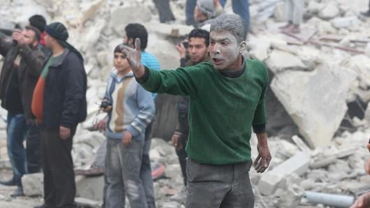 Ein junger Mann steht in Aleppo vor den Trümmern eines Hauses, das bei einem Luftangriff zerstört wurde. (Archivbild)