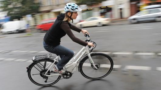 Eine Frau fährt mit einem Elektrofahrrad durch Berlin.