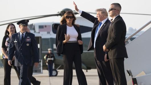 US-Präsident Donald Trump (2.v.r) und seine Frau, First Lady Melania Trump (3.v.r) vor ihrem Abflug nach Frankreich.
