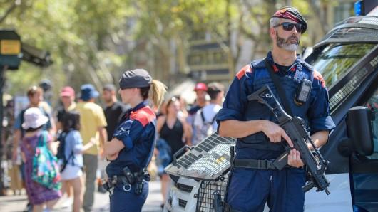Bewaffnete Polizisten stehen am 18.08.2017 nahe dem Bereich auf der Flaniermeile Las Ramblas in Barcelona (Spanien), auf dem Tags zuvor ein Lieferwagen in eine Menschenmenge gefahren war. Bei dem Terroranschlag auf der Promenade wurden am Donnerstag mehrere Menschen getötet und viele verletzt. Foto: Matthias Balk/dpa +++(c) dpa - Bildfunk+++