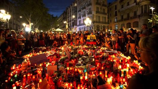 Menschen umringen am 18. August niedergelegte Blumen und Kerzen auf der Flaniermeile Las Ramblas in Barcelona.