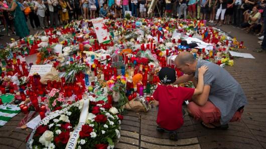 Blumen und Kerzen liegen am Anschlagsort in Barcelona.