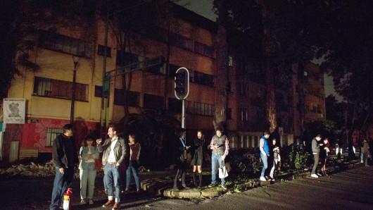 Menschen, die in Mexiko-Stadt während des Erdbebens aus einer Bar evakuiert wurden, stehen am 07.09.2017 kurz vor Mitternacht auf der Straße. Ein schweres Erdbeben der Stärke 8,0 hat sich vor Mexiko ereignet. Das Beben sei vor der Küste des Bundesstaates Chiapas im Süden Mexikos in einer Tiefe von 33 Kilometern registriert worden, teilte das Pazifik-Tsunami-Warnzentrum am Freitagmorgen deutscher Zeit mit. Foto: Rebecca Blackwell/AP/dpa +++(c) dpa - Bildfunk+++