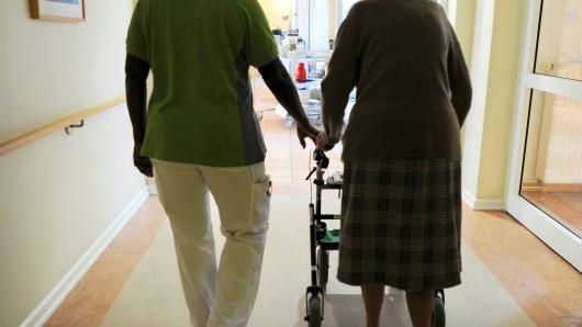 ARCHIV - Eine Pflegehausbewohnerin und eine Pflegehelferin gehen am 08.03.2013 in Hamburg in einem Seniorenzentrum mit einem Rollator einen Gang entlang. (zu dpa 175 000 mehr Menschen erhalten Pflegeleistungen vom 21.09.2017) Foto: Angelika Warmuth/dpa +++(c) dpa - Bildfunk+++
